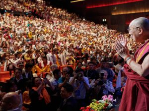 His Holiness the Dalai Lama greeting over 3100 members of the Tibetan community on his arrival on stage at the Palais du Congress in Paris, France on September 14, 2016. Photo/Olivier Adam